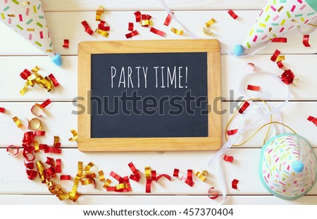 Party hat next to colorful confetti and blackboard on wooden table. Top view - stock photo