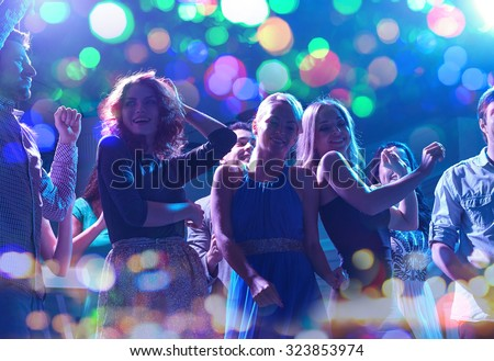 party, holidays, celebration, nightlife and people concept - group of happy friends dancing in night club - stock photo