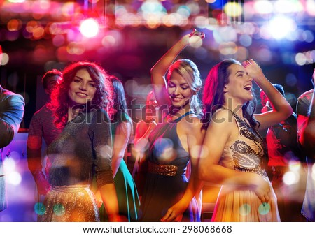 party, holidays, celebration, nightlife and people concept - happy friends dancing in club with holidays lights - stock photo