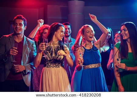party, holidays, celebration, nightlife and people concept - happy friends with glasses of champagne dancing in club - stock photo