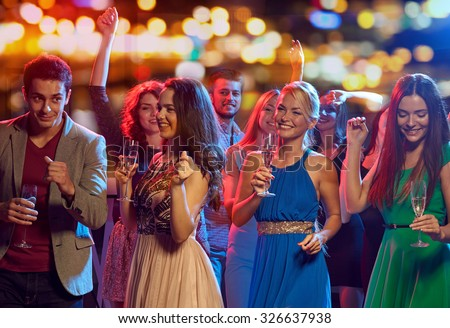 party, holidays, celebration, nightlife and people concept - happy friends with glasses of non-alcoholic champagne dancing at disco in nightclub - stock photo