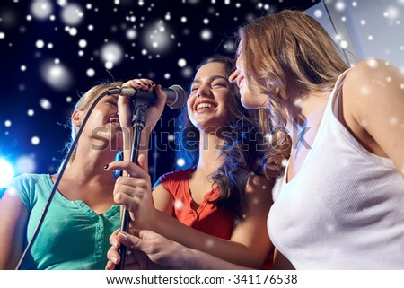 party, holidays, celebration, nightlife and people concept - happy young women singing karaoke in night club and snow effect - stock photo