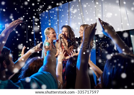 party, holidays, celebration, nightlife and people concept - happy young women singing karaoke on night club stage and snow effect