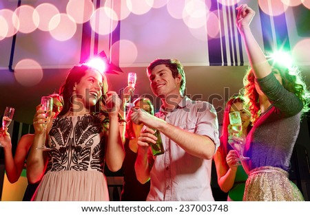 party, holidays, celebration, nightlife and people concept - smiling friends clinking glasses of champagne and beer in club - stock photo