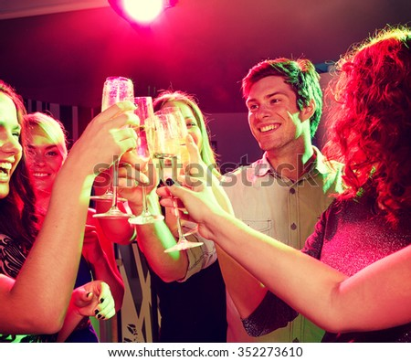 party, holidays, celebration, nightlife and people concept - smiling friends clinking glasses of champagne in club - stock photo