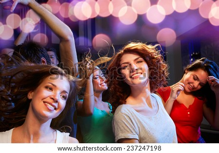 party, holidays, celebration, nightlife and people concept - smiling friends dancing at concert in club