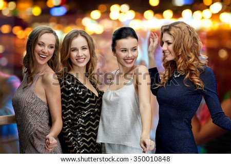 party, holidays, nightlife and people concept - happy young women dancing over night club disco lights background - stock photo