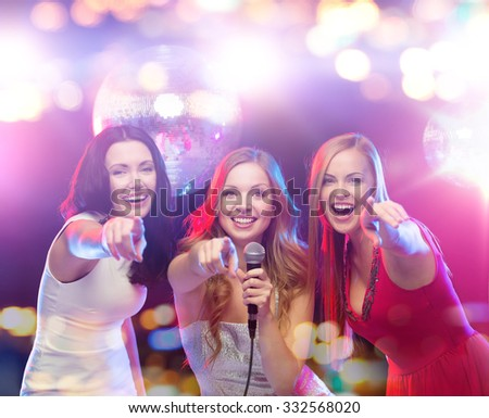 party, holidays, nightlife, entertainment and people concept - concept - happy women with microphone singing karaoke and pointing finger on you at night club - stock photo