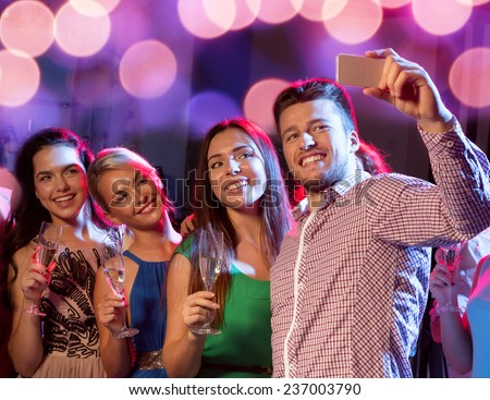 party, holidays, technology, nightlife and people concept - smiling friends with glasses of champagne and smartphone taking selfie in club - stock photo
