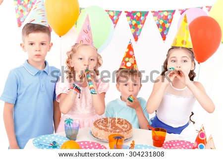 Party horn. Little cute kids sitting at adorned table with birthday cake on it and blowing party horn.