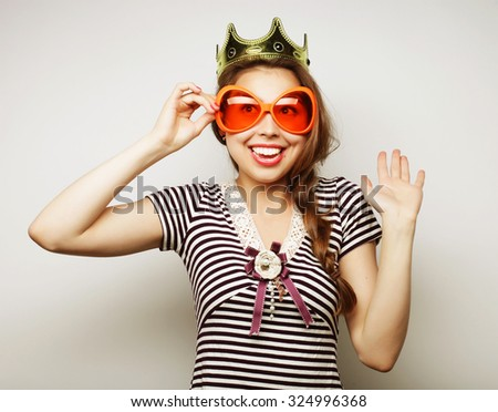 Party image. Playful young woman with big party glasses and crown. Ready for good time. - stock photo