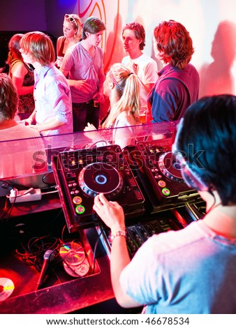 Party in a nightclub viewed from the DJ booth - stock photo
