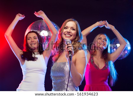 "party, ""new year"", celebration, friends, bachelorette party, birthday concept - three women in evening dresses dancing and singing karaoke"