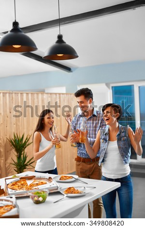 Party People. Happy Friends Eating Pizza, Drinking Beer And Having Fun Together Indoors. Young Cheerful People Having Dinner Party At Home. Holiday Celebration. Fast Food, Friendship, Leisure Concept. - stock photo