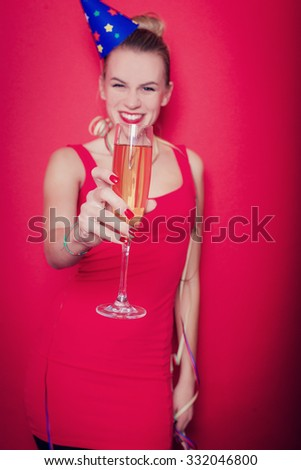 party photo of elegance sexy lady in red dress with red lips and blond beautiful hair, smiling and holding a wineglass with champagne