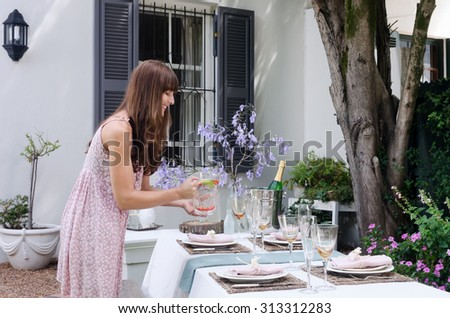 Party planner organising water for the table with simple place settings in a domestic garden environment