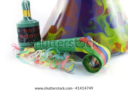 Party popper and blower with party hat and streamers on a reflective white background - stock photo