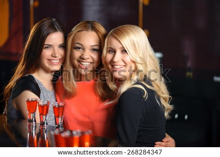 Party rocks. Beautiful cheerful women hugging each other and smiling to the camera when having a drink in the bar