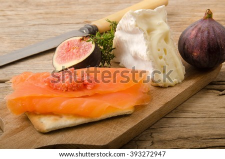 party snack with smoked slice irish wild salmon, fig, camembert and thyme on an old wooden board
