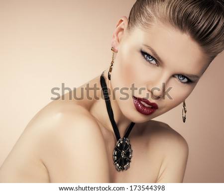 Party stiling glamour woman with beautiful jewelery. Close-up of young attractive female model with professional make-up and hairstyle posing in studio.  - stock photo