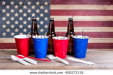 Party stuff for Fourth of July celebration with vintage wooden USA flag in background.