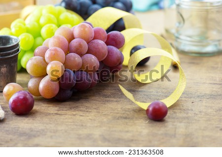 Party table with grapes. Fresh harvested red, black and white (green) grapes on a table, with table setting in background.  - stock photo