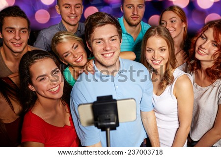 party, technology, nightlife and people concept - smiling friends with smartphone and monopod taking selfie in club - stock photo