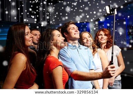 party, technology, nightlife and people concept - smiling friends with smartphone and monopod taking selfie in club and snow effect