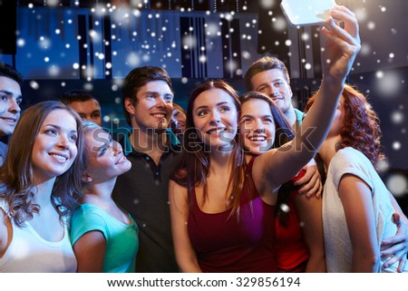 party, technology, nightlife and people concept - smiling friends with smartphone taking selfie in club and snow effect