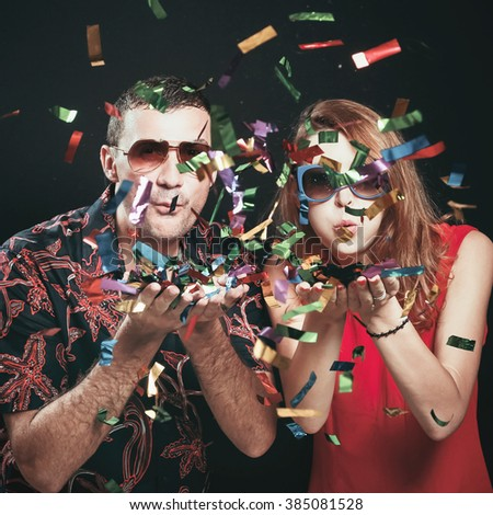Party time Two friends blowing confetti - celebration, party, fun concept - stock photo