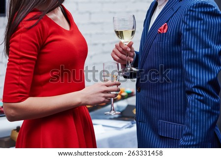 Party. Two guests of formal evening party celebration holding glasses of wine in their hands  - stock photo