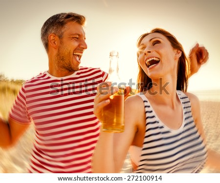 partying sunset couple dancing drinking - stock photo