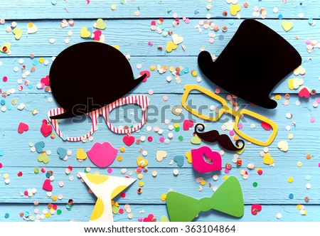 Partying with photo booth people composed of colorful accessories with a gent and lady in top hats and sunglasses sipping holiday cocktails surrounded by confetti on a blue wood background