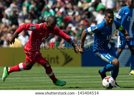 PASADENA, CA - JULY 7: Julia De Guzman #6 of Canada & Kevin Parsemain #17 of Martinique during the 2013 CONCACAF Gold Cup game between Canada & Martinique on July 7, 2013 at the Rose Bowl in Pasadena. - stock photo