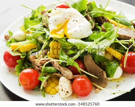 Pashot egg and salad with backed duck, rucola, cherry tomatoes, mozzarella and corn. Shallow dof. - stock photo