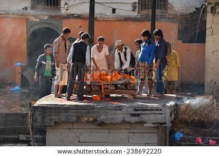 PASHUPATINATH - OCT 8: Human cremation along the holy Bagmati River at Pashupatinath, the second most important cremation place for Hindus, after Varanasi, India. Oct 8, 2013 in Kathmandu, Nepal - stock photo
