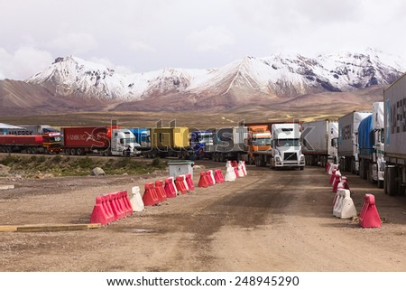 PASO CHUNGARA-TAMBO QUEMADO, CHILE-BOLIVIA - JANUARY 21, 2015: Trucks standing in line on the border of Chile and Bolivia at Chungara-Tambo Quemado on the way between La Paz-Arica on January 21, 2015 - stock photo