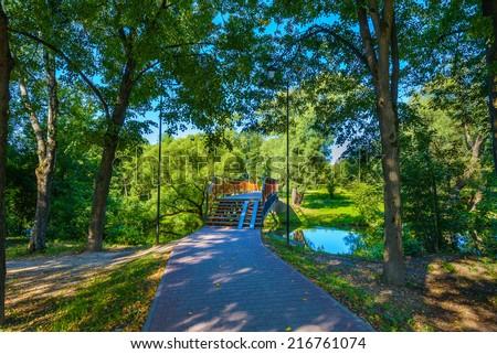 passage into the park through the old bridge - stock photo