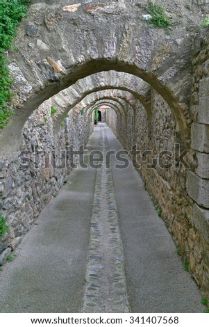 Passage under stone arches inside fortified town of Villefranche de Conflent in the Conflent region of Catalonia, Pyrenees-Orientales department, France - stock photo
