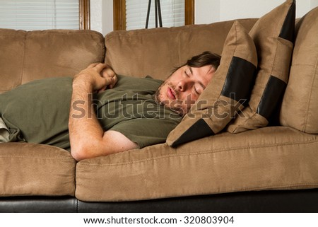 Passed out in an uncomfortable spot on the couch  - stock photo
