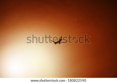 Passenger aeroplane after take off into the sun in orange sky, filter applied - stock photo