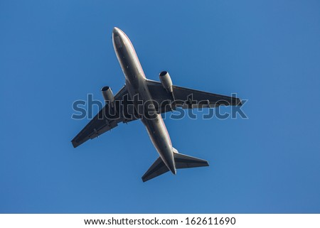 Passenger airplane against clear blue sky - stock photo