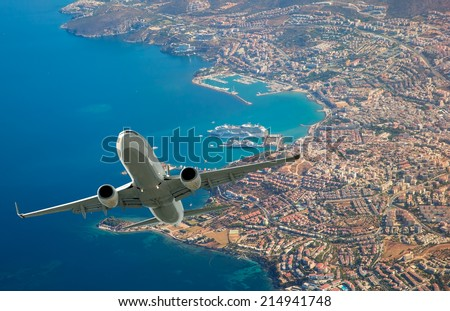 Passenger airplane flying above city - stock photo