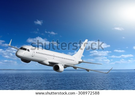 passenger airplane flying over the sea - stock photo