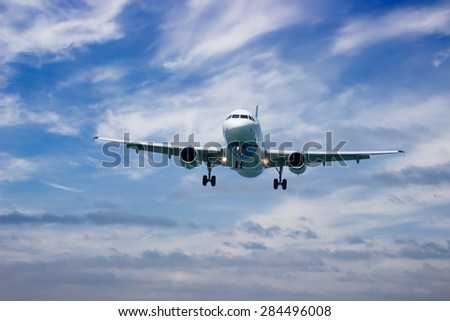 Passenger airplane landing at sunset in cloudy weather - stock photo