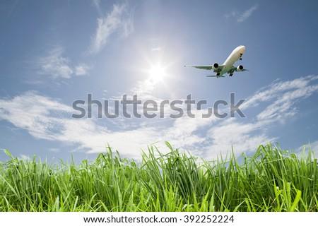 Passenger airplane landing on blue sky background. - stock photo