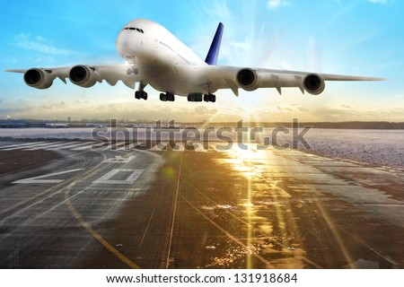 Passenger airplane landing on runway in airport. Evening. - stock photo