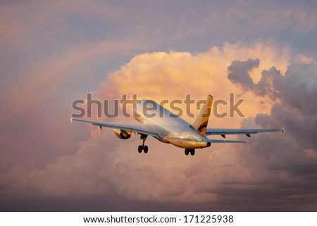 Passenger airplane taking off at sunset - stock photo
