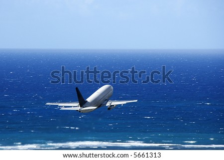 Passenger airplane taking off from airport headed over the Pacific ocean. - stock photo