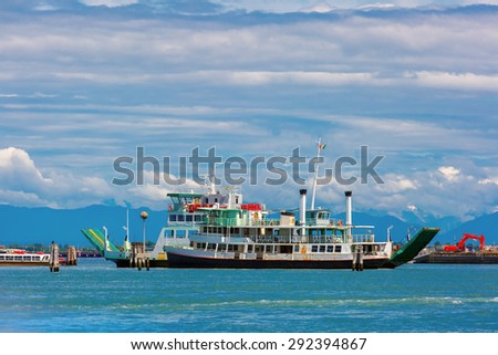 Passenger and cargo ships in the Venetian lagoon on the background of the sea, sky and mountains summer sunny day, Venice, Italy